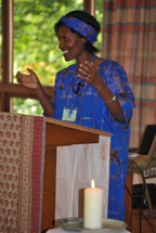 A women in a traditional blue Kenyan dress speaking from a lectern.