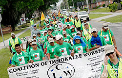 A group of marchers in green t-shirts, holding a white sign.