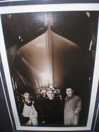 A black and white photo of three men standing under the bow of a boat