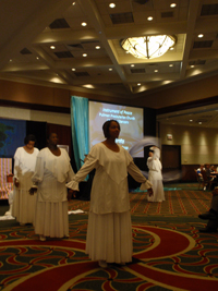 A worshipper in white clothing stands with her arms out, with other worshippers in white behind her in a large room.