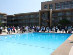 A large group of people standing around an outdoor swimming pool