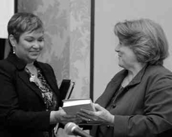 In black and white, a woman receives a book from another woman.
