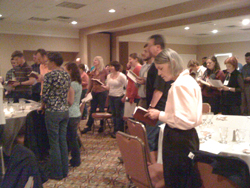 A group of people in worship, standing, holding books in a convention center room.