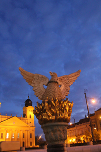 A statue of a phoenix raising out of ashes in a square, beneath a dark blue sky.