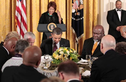 A woman delivers an invocation from a podium, while Barack Obama and other religious figures are seated in front of it, praying.