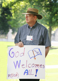 Cliff Kirkpatrick holding a sign at a demonstration.