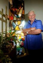 Ralph Waite, standing in a shadowy space in front of a lit stained glass window and beside two large crosses and a plant.