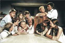 "A group photo of all the actors of ""The Waltons"" in character, sitting at a table."