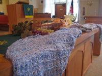 Pastel-colored prayer shawls on a wooden communion table in a sanctuary of a church.