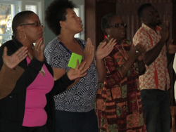A group of men and women singing and holding up their hands in worship.