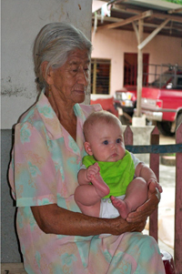 An older woman holding a baby in her lap.