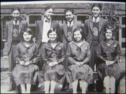 An old black and white photo of young men and women, dressed up and gathered together for a photo.