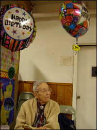 "The Rev. Walter Soboleff, sitting in a chair, with ""Happy Birthday"" ballons floating above him."