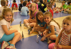 A group of girls sitting on a floor with other kids.