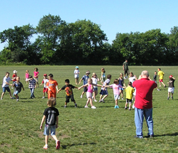 A group of kids hold hands and play in a grassy field with supervisors.