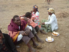 A small group of men and women sitting on the ground with two plates of food.
