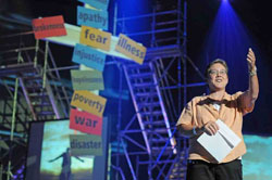 A man on a stage with a cross covered in colored papers lifts his hand during a sermon.