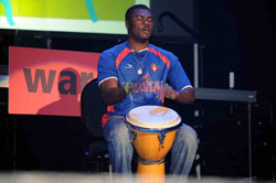 A young man sitting on a stage, beating awooden drum.