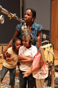 A woman with a group of three children, recording a song into a microphone.