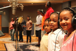Three children wearing headphones in a recording studio with other people.