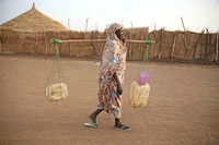 Woman carries empty jerry cans seeking water - photo by Hannah McNeish