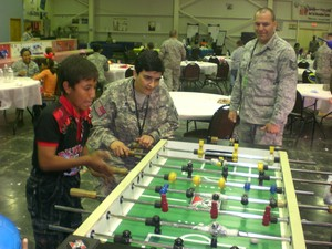 Soldiers play foosball with a boy