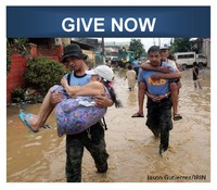 Photo of men carrying survivors through a flooded street