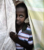 A boy peeks out of a tent