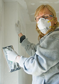 Woman wearing a mask, working on dry wall