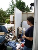 survivor of a tornado stands amidst her destroyed home