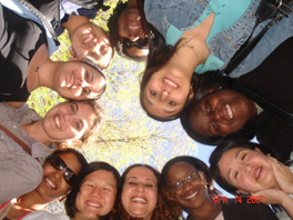 Photo of several young women gathered into a circle looking down at the camera