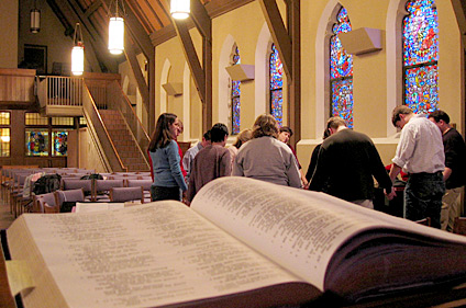 Bible in the foreground, group of people holding hands in a circle and praying in the background.