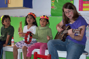 Photograph of a YAV singing with three young children.