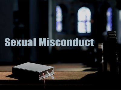 "Bible on kneelers in church sanctuary w/ text ""Sexual Misconduct"""