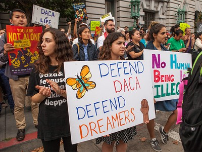 Protesters hold various signs and banners at a DACA rally in San Francisco September 5, 2017.