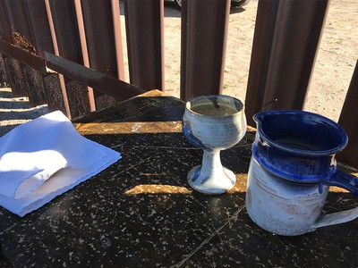 Image of communion ware set up at the border wall in Texas.