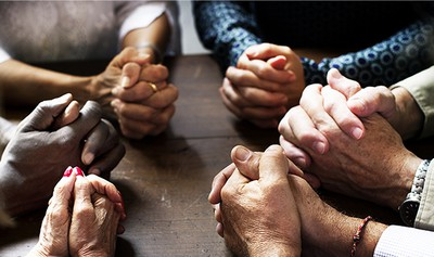 Group of people with interlocked fingers praying together