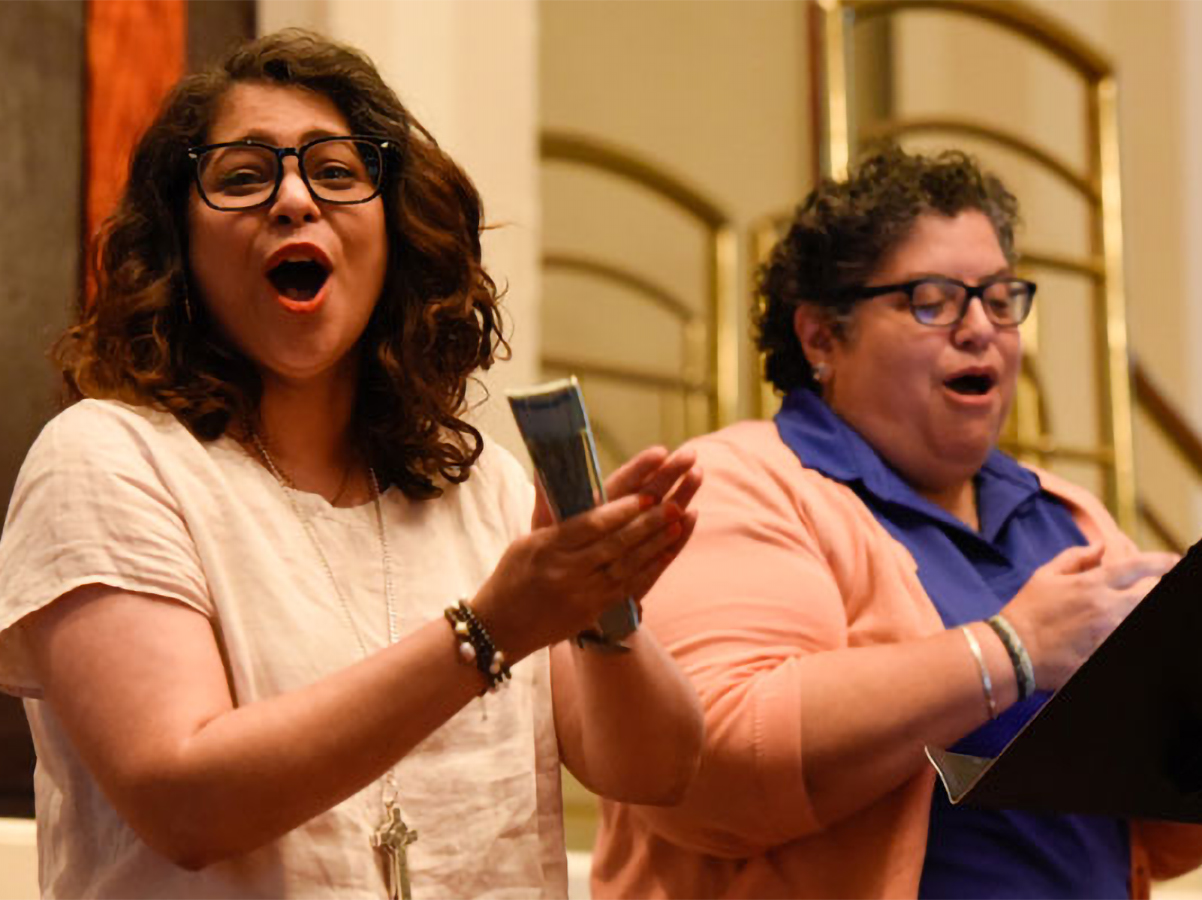 General Assembly Co-Moderator and Ruling Elder Vilmarie Cintrón-Olivieri joins Marissa Galvan-Valle to help lead the Big Tent plenary in singing Thursday. (Photo by Rich Copley)
