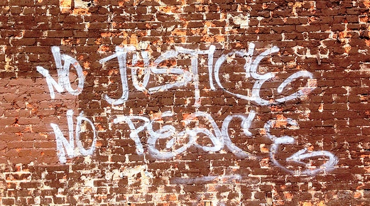 "Image is a worn red brick wall with ""No Justice No Peace"" written across it in white graffiti style lettering (all caps)"