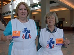 Photo of two women wearing white bibs with the Presbyterian seal
