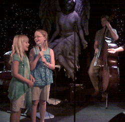 Photo of two young girls singing on stage