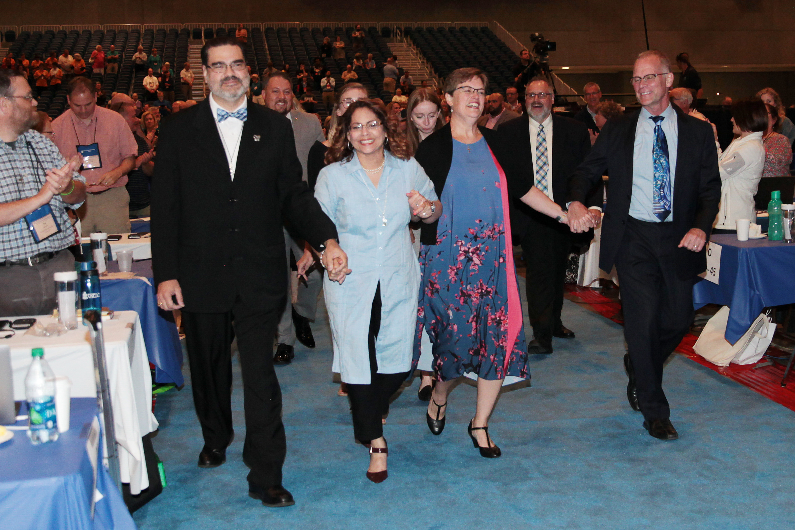 Vilmarie Cintrón-Olivieri (center-left) and Cindy Kohlmann (center-right) enter the plenary hall after their election as co-moderators. Photo by Danny Bolin.