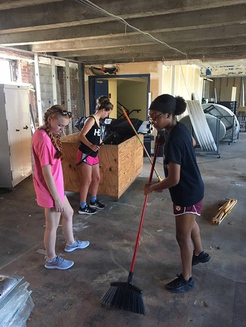 Young volunteers help clean up a work site as part of their Hands and Feet experience at Amen House in St. Louis.