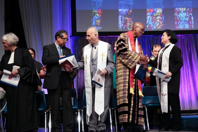 In Christ there is no east or west. Stated Clerk J. Herbert Nelson (second from right), with Rev. Najla Kassab (right), asks Presbyterians and Ecumenical friends Pass The Peace in Wednesday's Ecumenical Service of Worship.