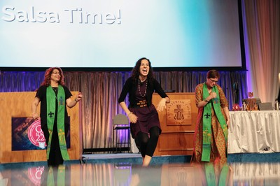 Samantha Gonzalez-Block, associate pastor of Grace Covenant Presbyterian Church in Asheville, NC, leads a salsa dance break during the afternoon plenary session Thursday at the 223rd General Assembly.
