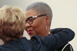 Katharine Henderson and Traci Blackmon embrace after Auburn Seminary breakfast