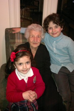 Genocide survivor smiles proudly with her great grandchildren.