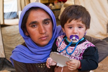 A Yazidi woman and her young daughter narrowly escaped ISIS forces. They, along with her husband Guly Badal Jerdo and other children, found refuge in one of many internally displaced persons (IDP) camp locations in Khanke, Iraq. (Aug. 29, 2014)