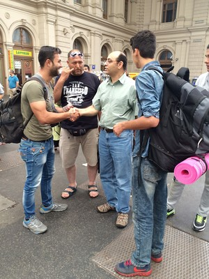 Amgad Beblawi talks with young men from Syria about their train tickets.