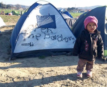 A child stands outside a tent at a refugee camp on the Macedonia-Greece Border.